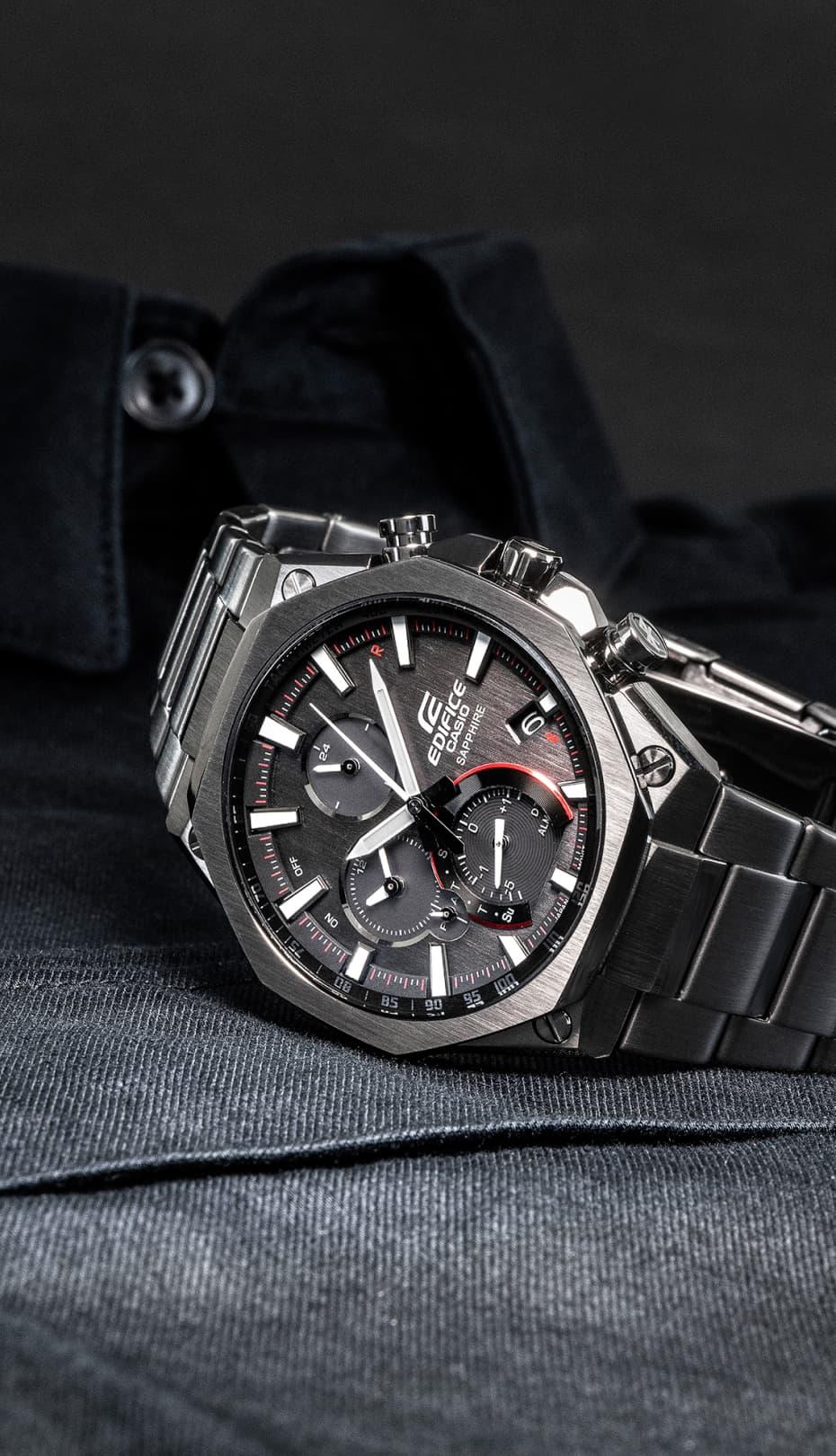 reloj rojo y gris de metal sobre una camisa de hombre