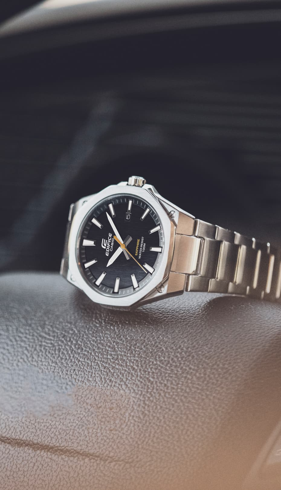 reloj plateado de CASIO sobre un volante de coche