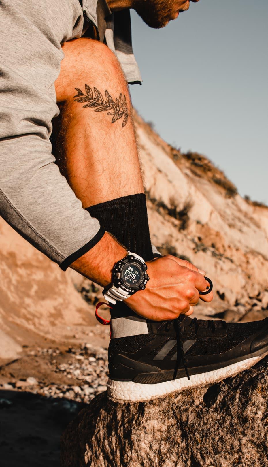un hombre atándose los cordones de las zapatillas con un reloj CASIO g shock