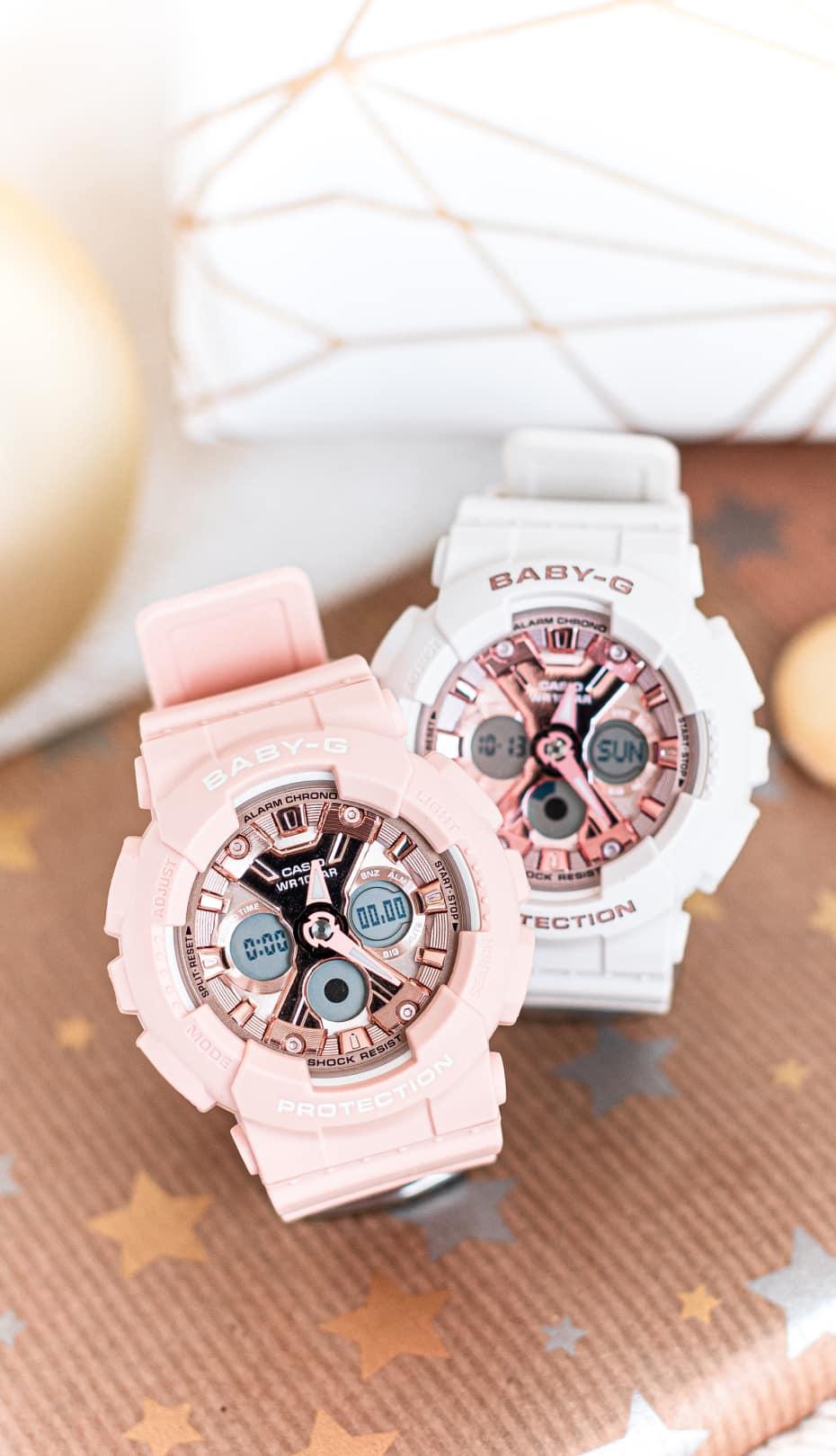 un reloj rosa y otro blanco de Baby-G CASIO sobre de papel de regalo