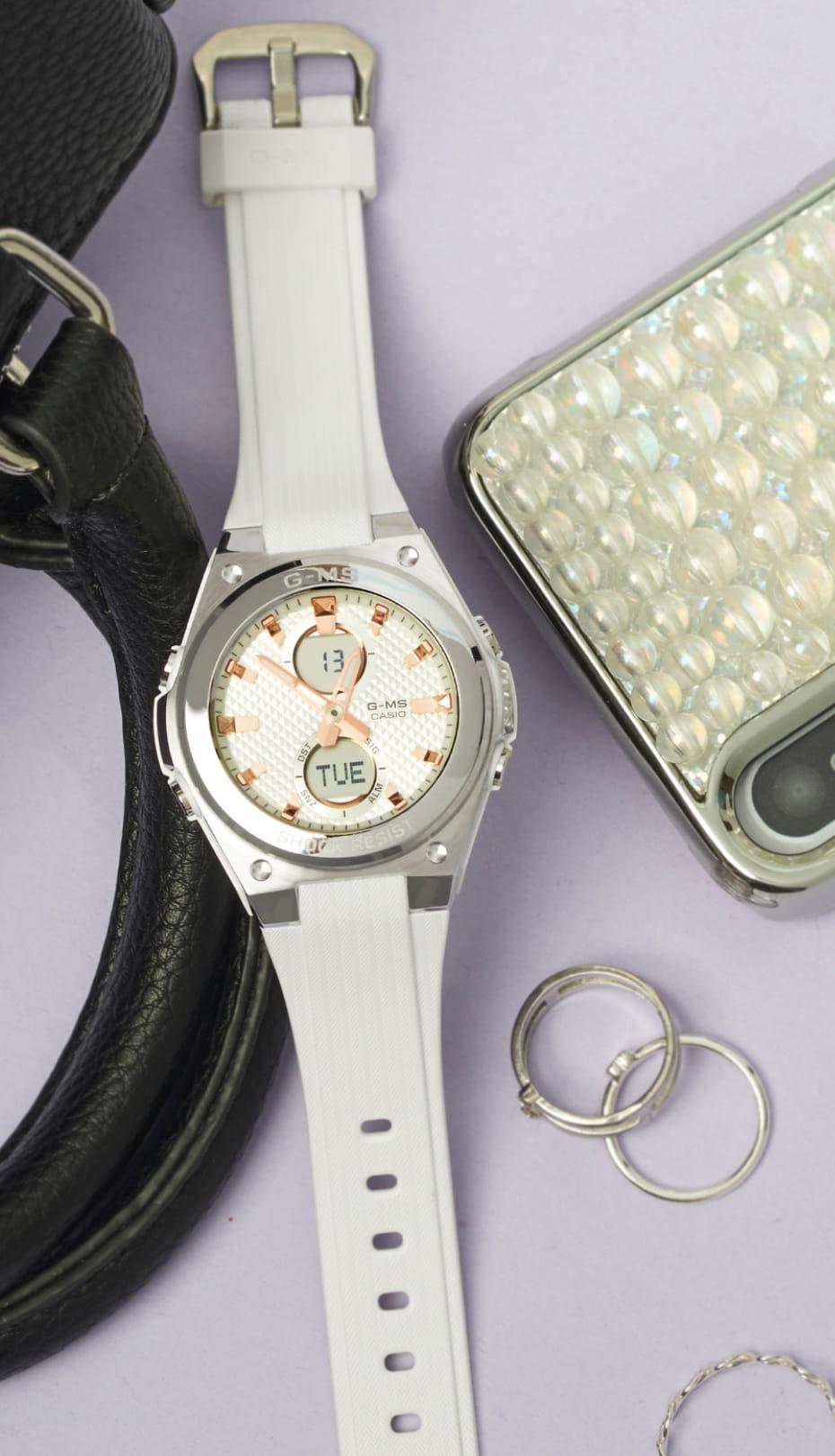 reloj blanco Baby G de CASIO entre anillos, móvil y bolso