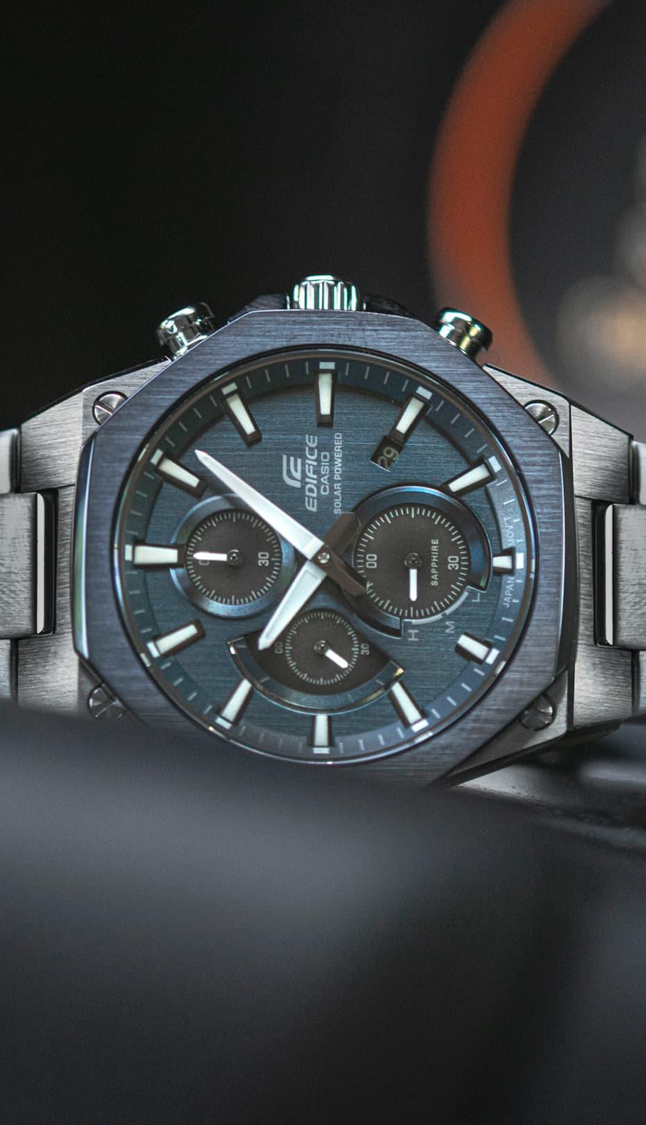 reloj gris y azul de metal de CASIO sobre el salpicadero de un coche
