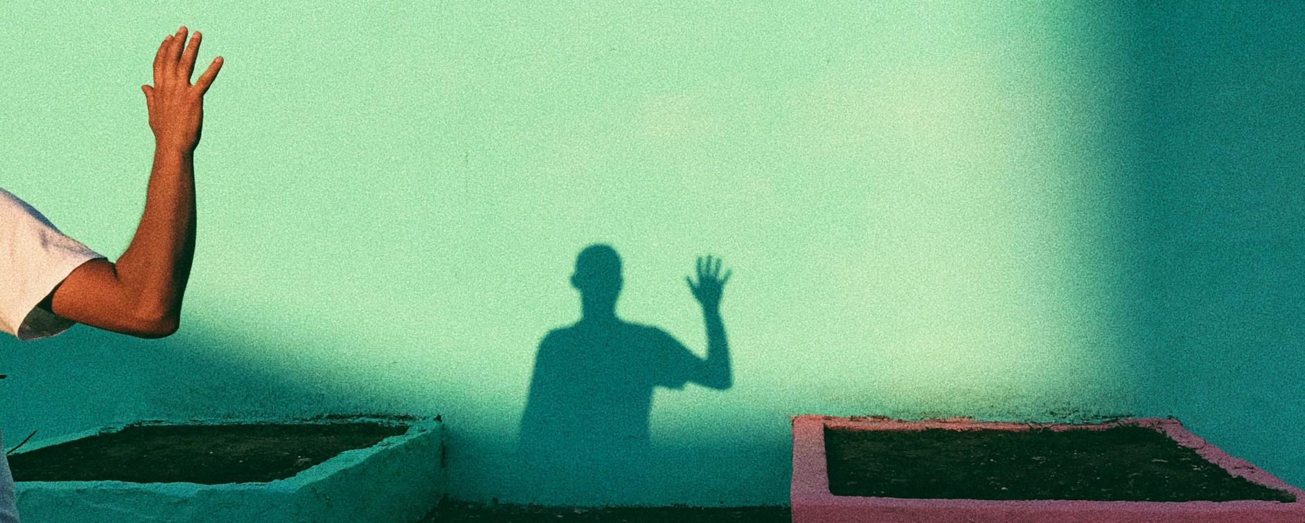 Sombra de hombre saludando