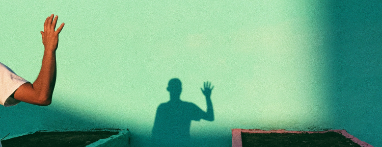 Sombra de un hombre saludando